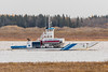 Barge Niska I on the Moose River heading from Moosonee to Moose Factory Island with fuel trucks on board.
