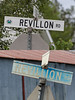 Revillon Road sign in Moosonee at Revillon and Fourth Street above sign reading Revillion Road at Sixth Street. Correct spelling is Revillon.