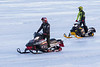 Two snowmobiles with riders standing on the Moose River.