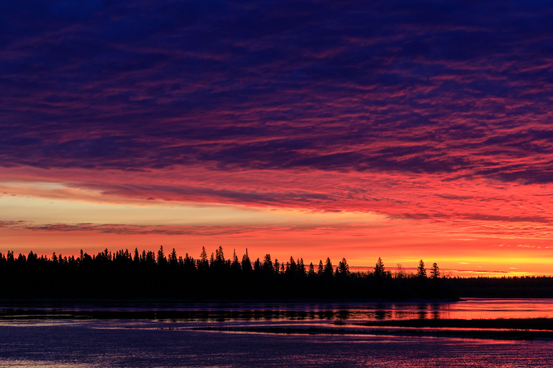 Purple sky before sunrise over Butler Island reflected in the water of the Moose River at Moosonee.