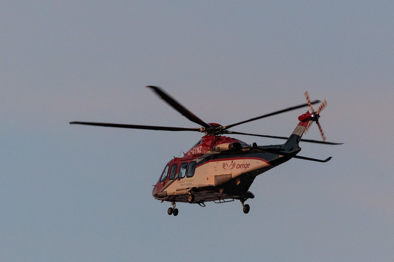 ORNGE helicopter C-GYNZ over the Moose River at Moosonee around sunset 2017 May 26th.