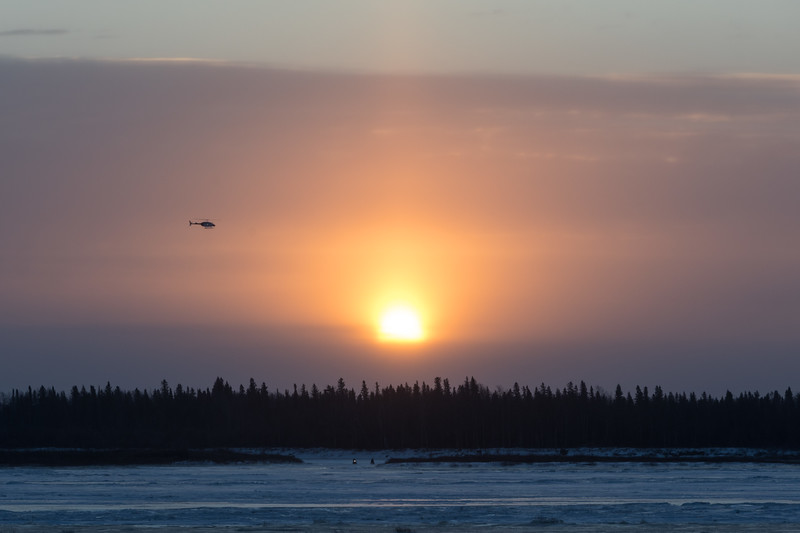 Sun rising over low clouds across the Moose River from Moosonee. 2017 December 7th. Helicopter and snowmobiles.