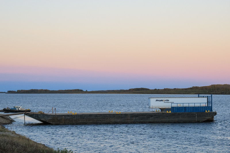Small tug Harricana River and a barge with a trailer on the Moose River at Moosonee.