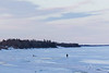 Two dogs and woman walking down the Moose River around sunset.