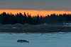 Thin band of colour along the horizon at sunrise across the Moose River from Moosonee. 2017 January 17th. Truck driving on the Moose River.