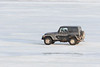 Jeep driving along the Moose River shoreline in Moosonee.