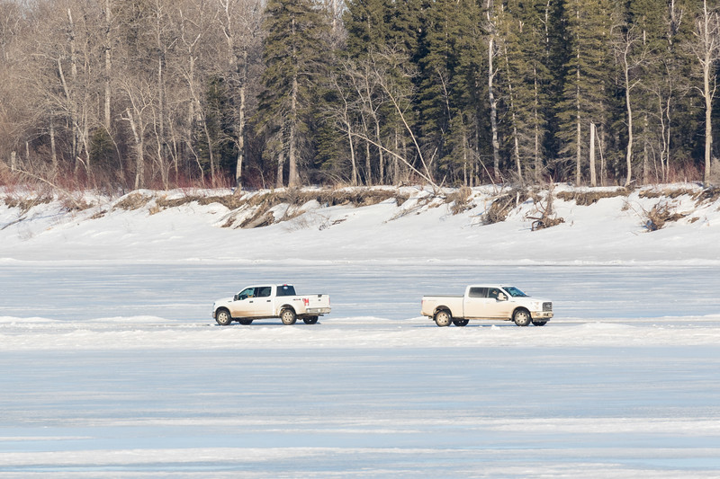 Two white trucks passing in front of Butler Island in the Moose River at Moosonee.