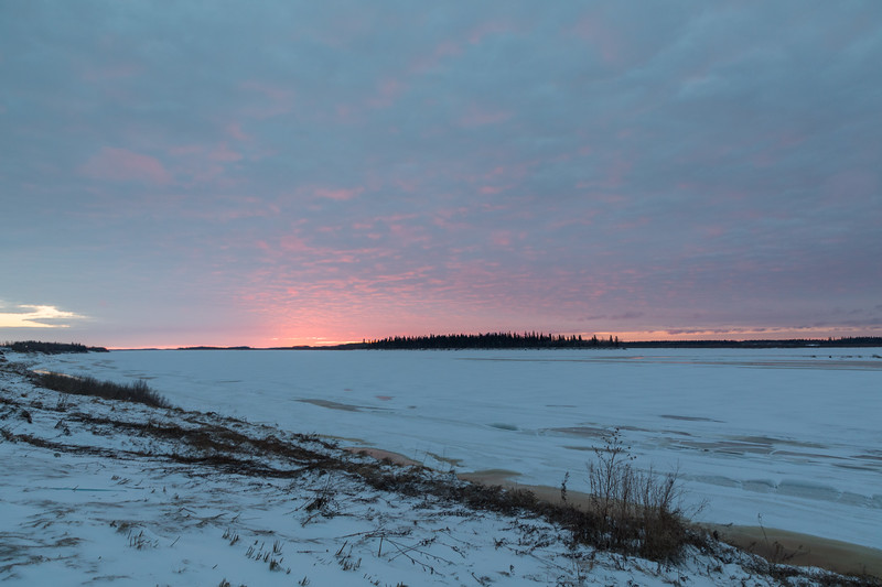 Just before sunrise, looking across the Moose River from Moosonee. Colours in the clouds are fading as sunrise approaches.
