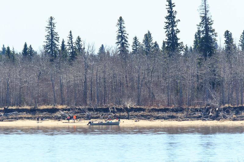 People enjoying beach on Charles Island 2017 May 20th. Canoe on the beach. Backlit.