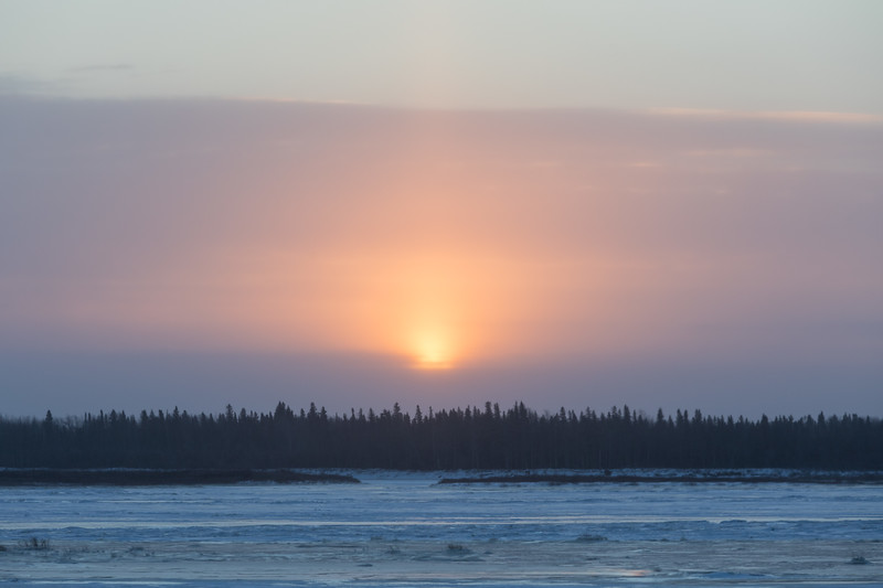 Sun rising over low clouds across the Moose River from Moosonee. 2017 December 7th.