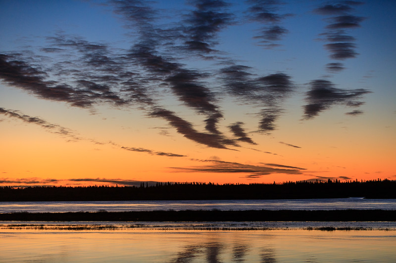 Sky before sunrise across the Moose River from Moosonee reflected in the water.