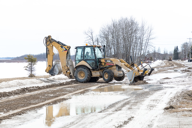 Loader scraping frozen road.