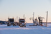 Trucks and old fuel loading equipment along the Moose River in Moosonee.