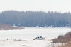 Vehicle turning on the edge of the Moose River after bringing goods to snowmobile taxis.