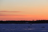 Looking across the Moose River on a cold morning just before sunrise. Vehicle driving across the river.
