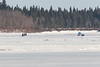 Two snowmobile taxis on the Moose River. Distortion from heat waves in this shot taken at ice level.