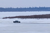 Truck driving to Moosonee across the Moose River. Water on the ice on a warm 8C afternoon.