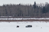 Walkers getting picked up by a snowmobile on the Moose River as a taxi drives by.