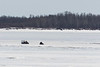 Snowmobile and ATV with sled on the Moose River at Moosonee 2017 April 12th.
