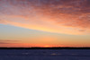 Looking across the Moose River on a cold morning just before sunrise. Lights of vehicle driving across the river.
