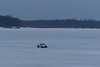 Truck driving across the Moose River to Moosonee on an overcast morning.