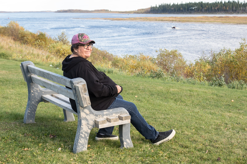 Denise Lantz sitting on a bench above the Moose River near the Moosonee Lodge.
