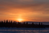 Sunrise across the Moose River from Moosonee. Ice on the river reflects the sky.