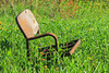 Old chair in the grass near water tower.