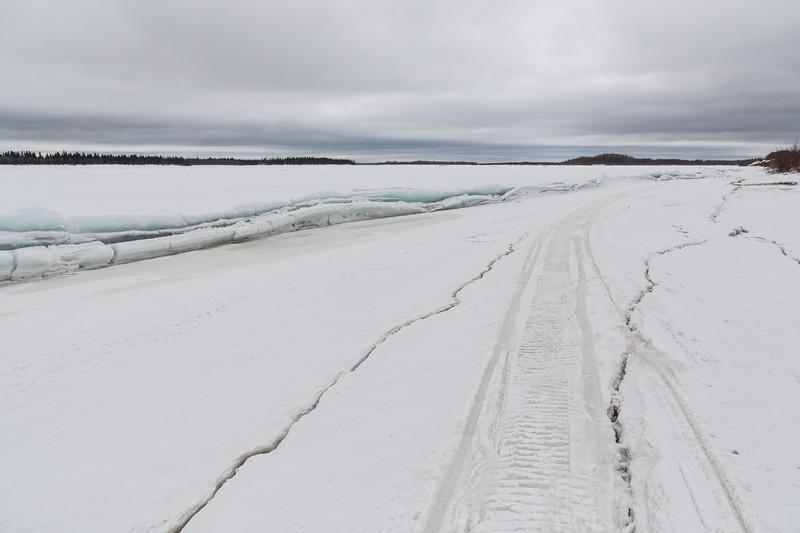 Cracks and broken ice along the Moose River shoreline.