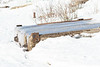 Flowing water frozen in place on public dock support block.