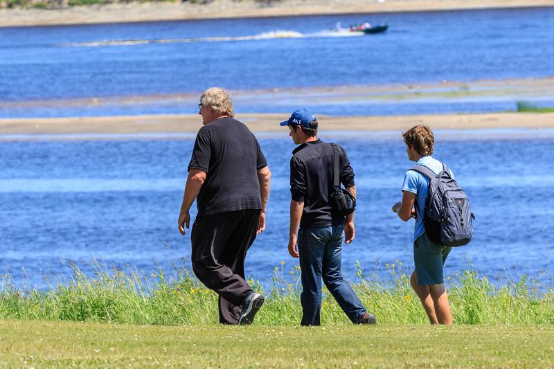 People walking along the river bank.