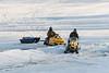 Two snowmobiles with sleds on the Moose River.