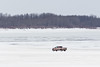 Red truck driving across the Moose River 2017 April 3rd.