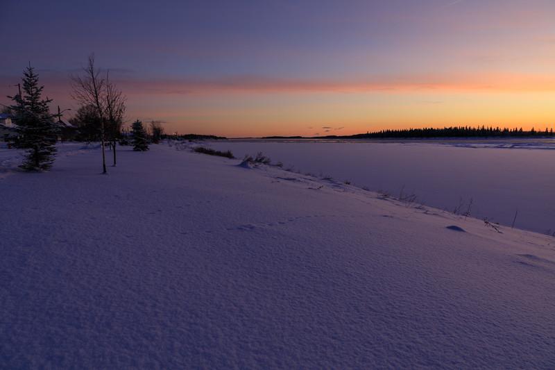 Moose River shoreline in Moosonee before sunrise looking down the river.