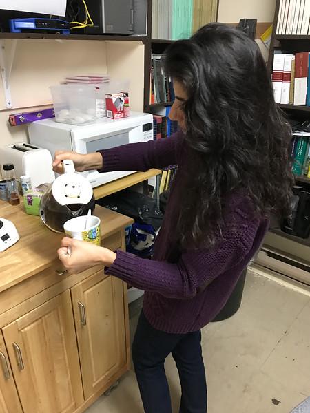 Articling student Ruchi Punjabi pouring coffee at Keewaytinok Native Legal Services.