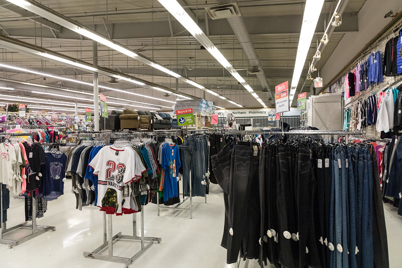 Clothing and furniture section at Moosonee with pharmacy in background.