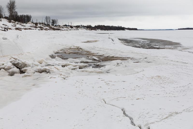 Water and broken ice along the tidemark, looking down the Moose River in Moosonee.