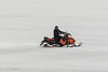 Snowmobile moving through slush on top of the ice of the Moose River.