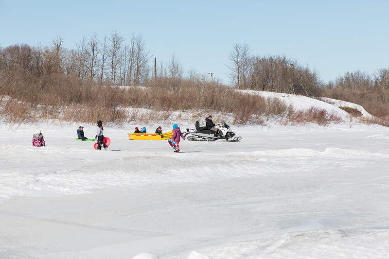 Snowmobile and sledders at the bottom of McCauley's Hill.