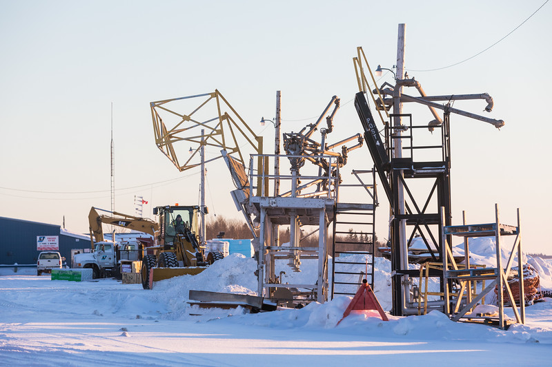 Old fuel loading equipment and snow clearing along the Moose River in Moosonee.