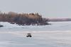 White pickup truck driving along the Moose River shoreline in Moosonee.