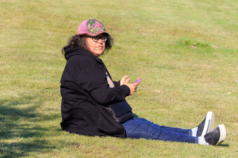 Denise Lantz using her iPhone while sitting on the shore of the Moose River.