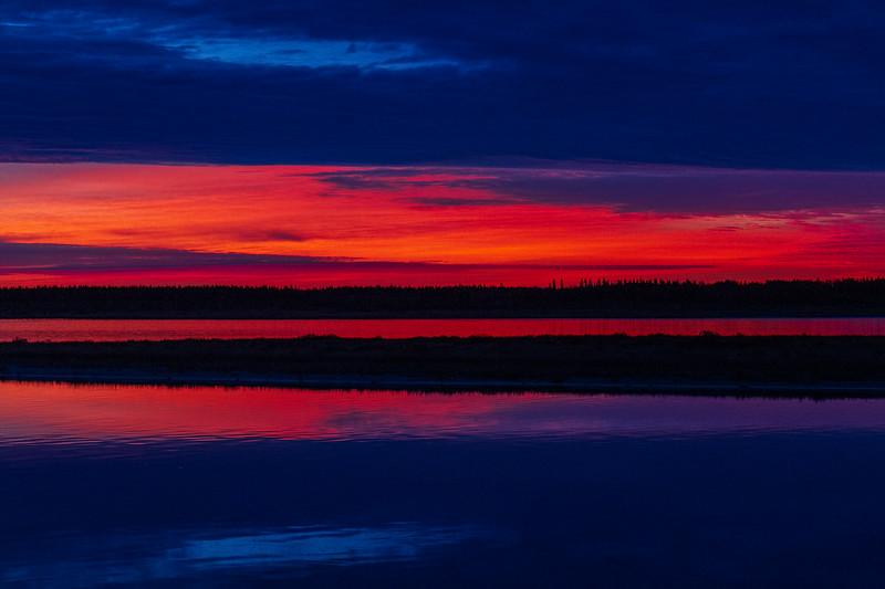 Looking across the Moose River before sunrise. Low purple skies under dark clouds.