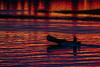 Canoe in silhouette on water reflecting purple and yellow from the sky before sunrise. 2018 October 22