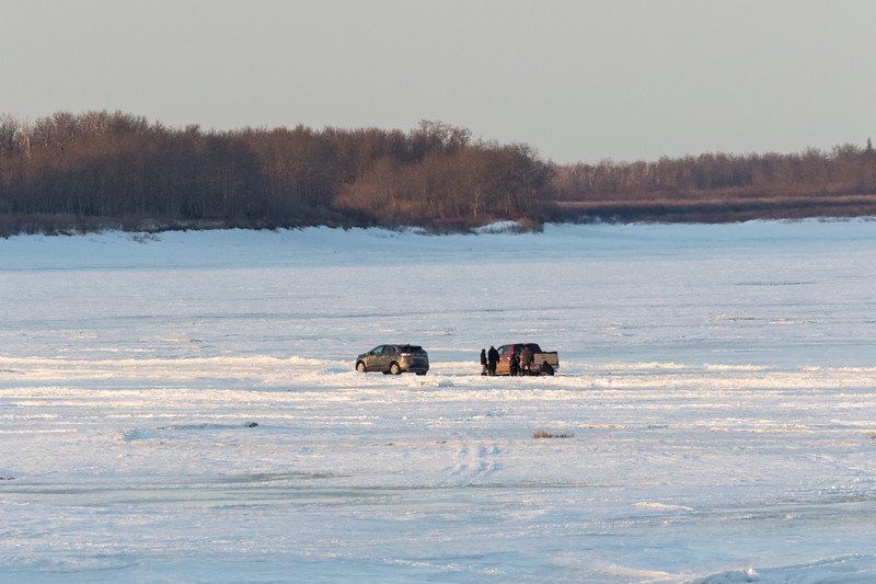 People and vehicles on the Moose River at Moosonee.