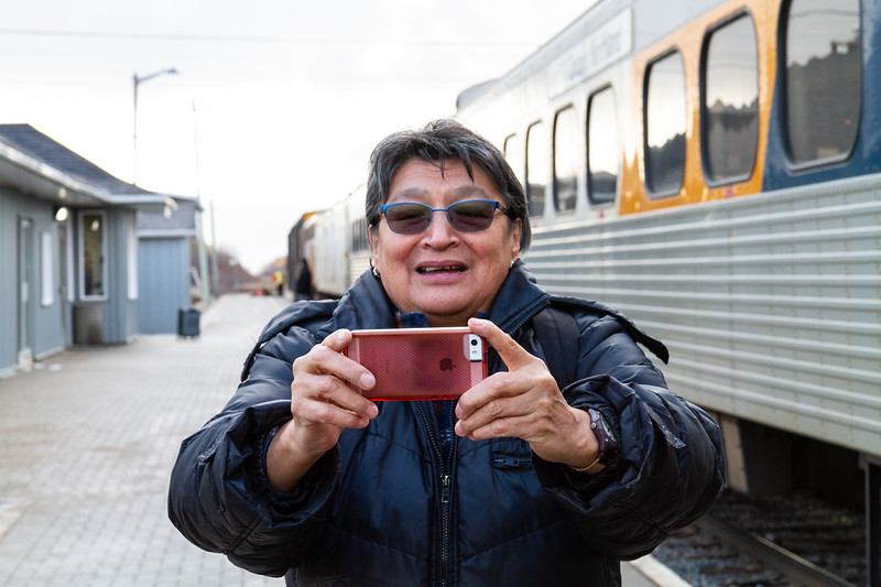 Celine Koostachin taking photograph at tran station