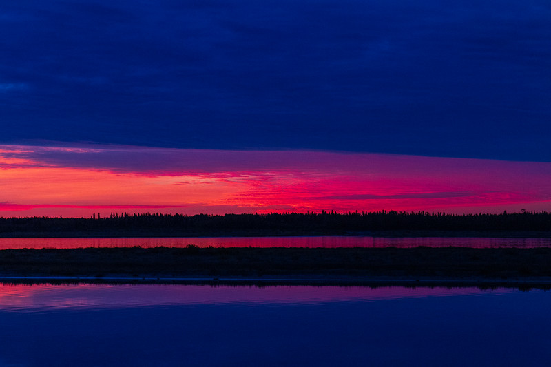 View across the Moose River before sunrise. Dark clouds above purple skies and water. 2018 October 8.