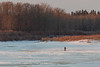 Man walking on the Moose River shorly after sunrise. 2018 April 26th.