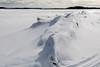 Snow covered tide mark along the Moose River at Moosonee.