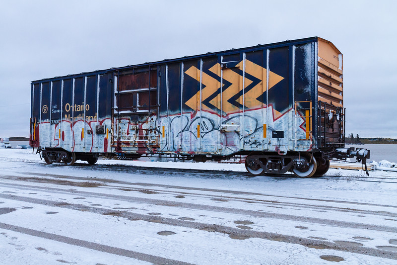 Boxcar ONT 7700 along the Moose River above barge docks in Moosonee.